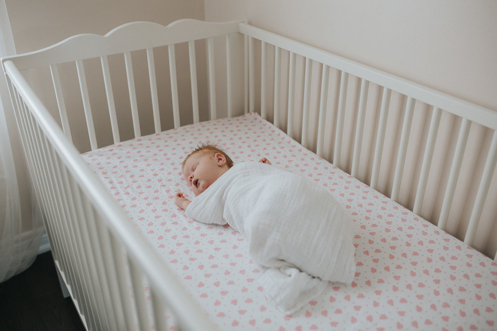 2 week old swaddled baby girl with red hair asleep in nursery crib - Stouffville In-Home Photos