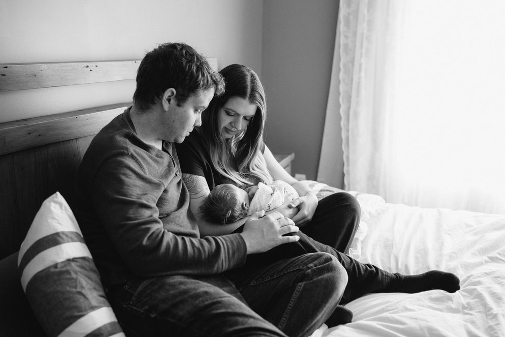 family of 3, new parents sitting on bed holding and looking at 2 week old baby girl with red hair - Stouffville Lifestyle Photography