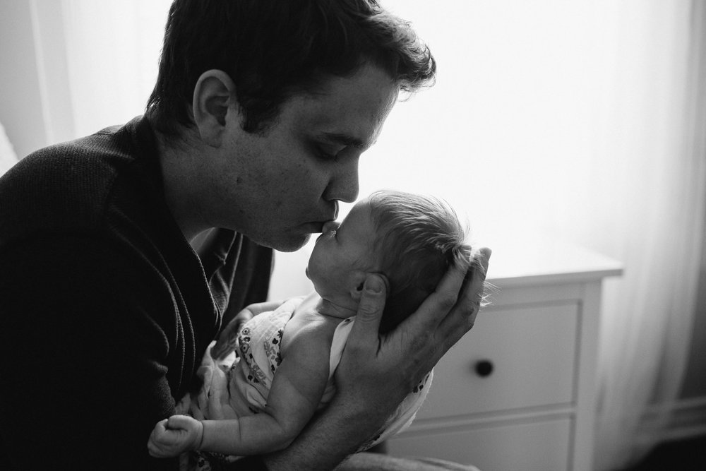 first time dad sitting in nursery chair holding sleeping 2 week old baby girl, kissing her nose - Markham In-Home Photography