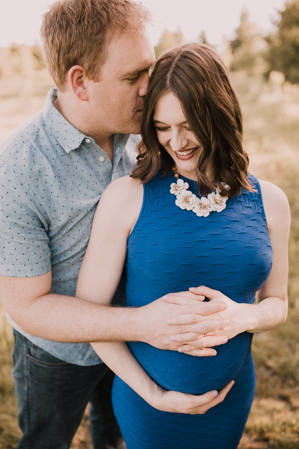 husband embraces pregnant wife in blue dress and kisses her on cheek at sunset - Newmarket Outdoor Photography