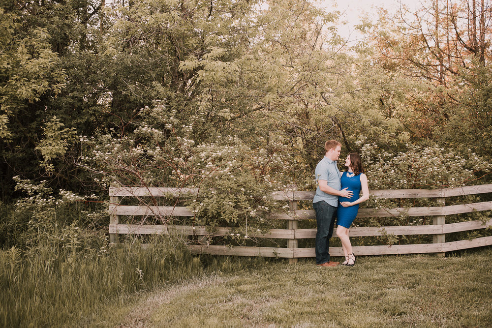 pregnant brunette mom-to-be in blue dress leaning against fence with husband, smiling at him - Newmarket Lifestyle Photos