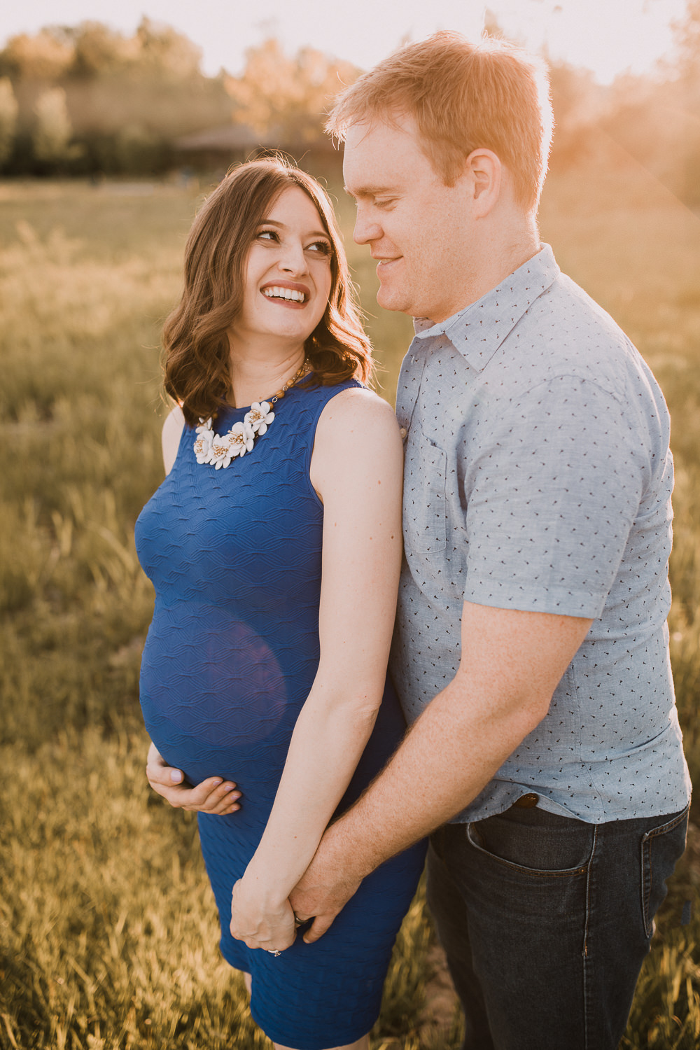 pregnant brunette mom-to-be in blue dress holding husband's hand and smiling at him - Stouffville Lifestyle Photos