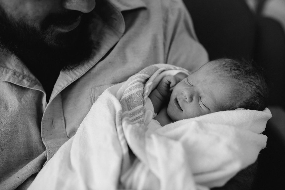 new dad sitting in hospital chair holding sleeping, smiling 10 hour old baby boy - Markham In-Hospital Photography