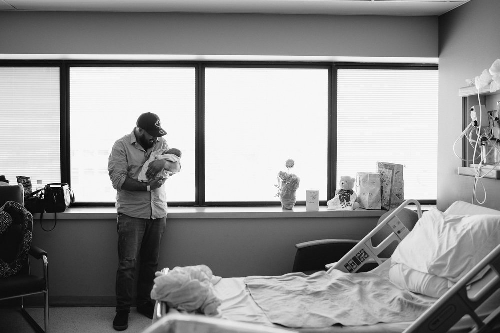 new dad standing in hospital room holding swaddled, sleeping 10 hour old baby boy - Barrie In-Hospital Photography