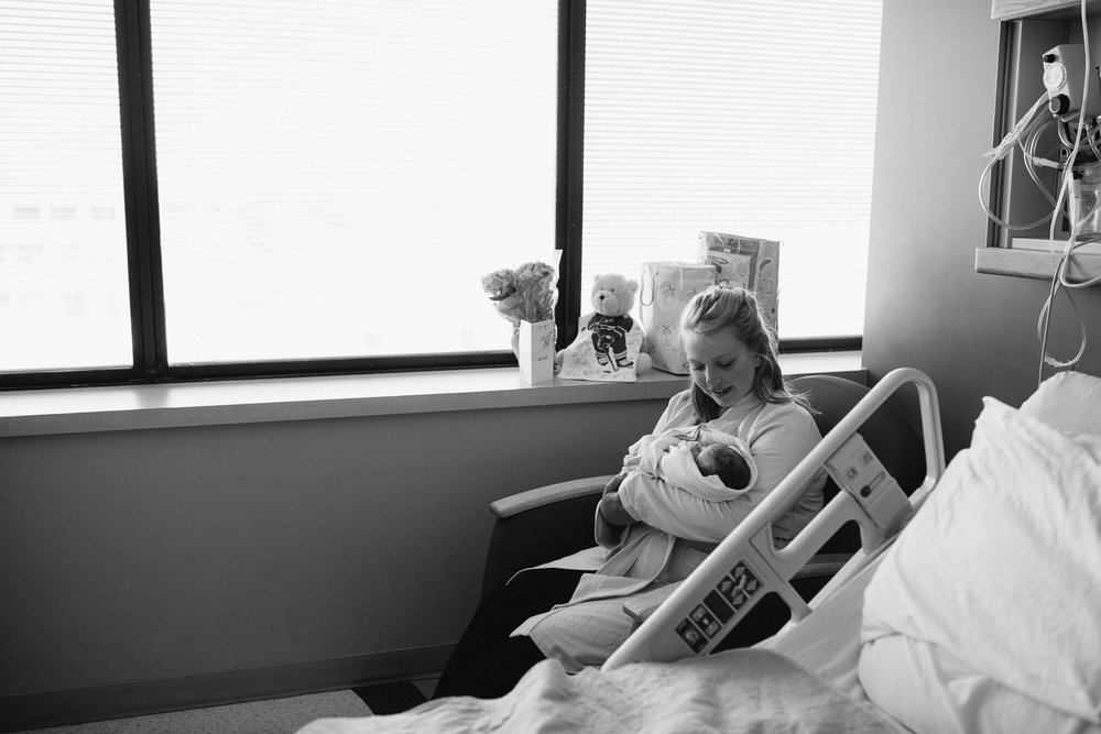 new mother sitting in hospital chair holding swaddled 10 hour old baby boy - Newmarket In-Hospital Photography