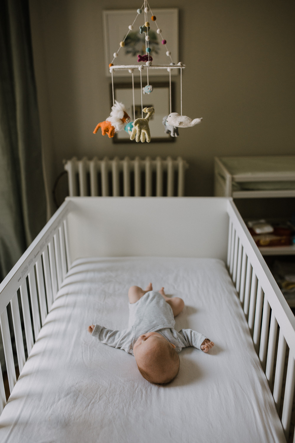 2 week old baby boy in grey onesie sleeping in nursery crib - Barrie Lifestyle Photography