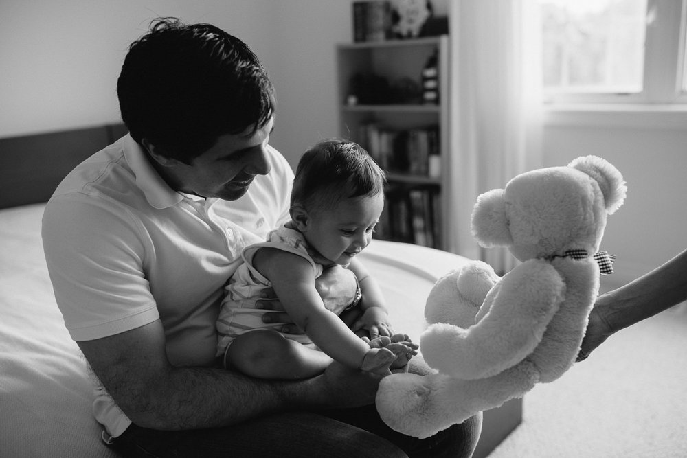 father sitting on bed with 8 month old baby boy in his lap, baby reaching for teddy bear offered by mother - Newmarket In-Home Photos