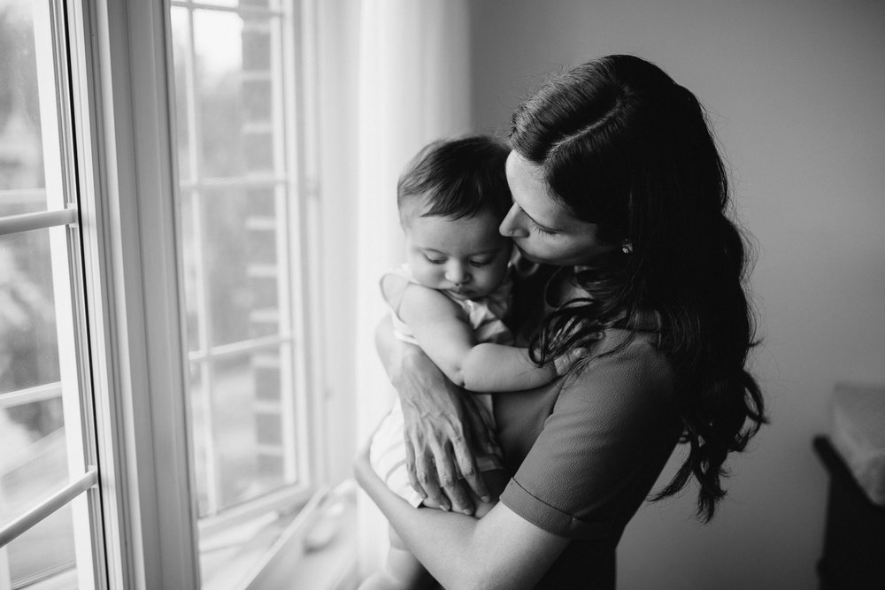 mom standing at window embracing 8 month old baby boy - Stouffville Lifestyle Photos
