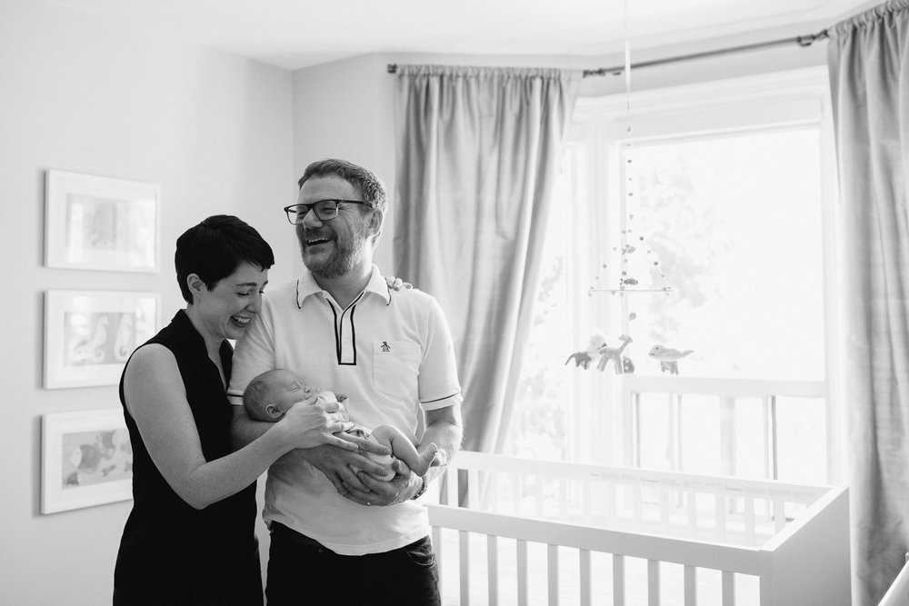 laughing parents standing in nursery holding sleeping baby boy - Barrie In-Home Photography