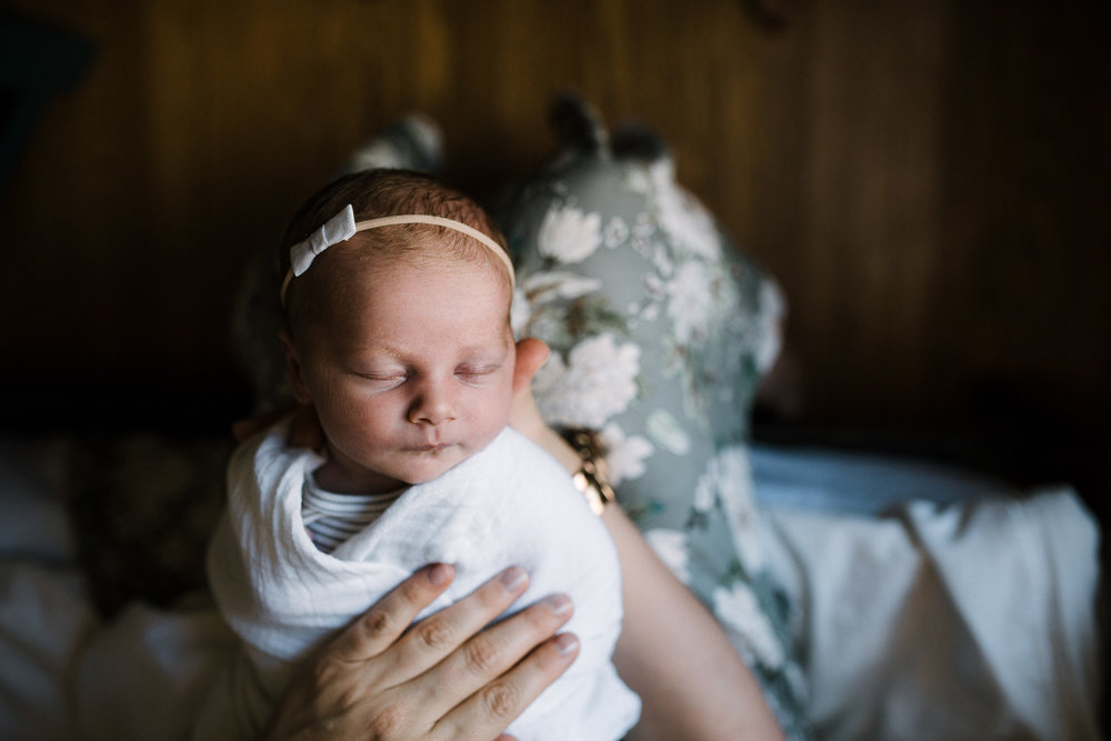 2 week old swaddled baby girl with headband on sleeping in mom's lap - Newmarket In-Home Photos