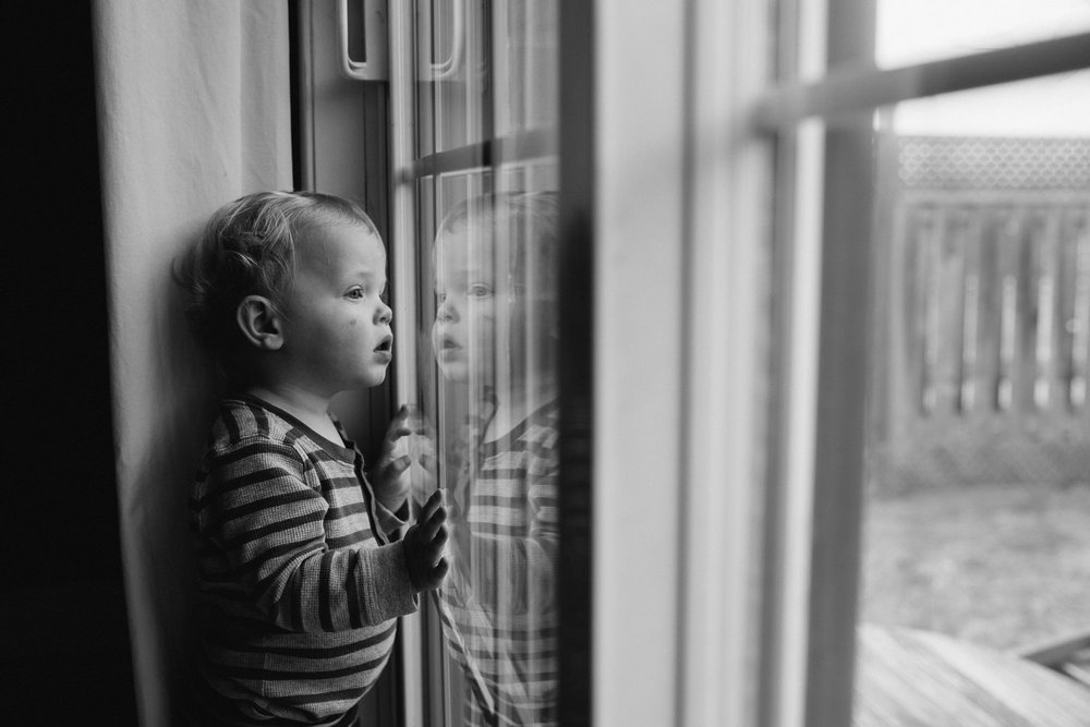 blonde 18 month old boy standing at window looking outside, can see reflection - Markham Family Photographs