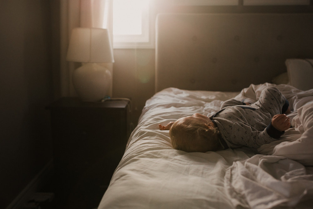 blonde 18 month old toddler lying on bed as golden setting sun streams through window - Stouffville Documentary Photography