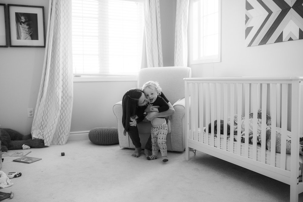 mom kissing and hugging 18 month old son in nursery - Newmarket Documentary Photographer