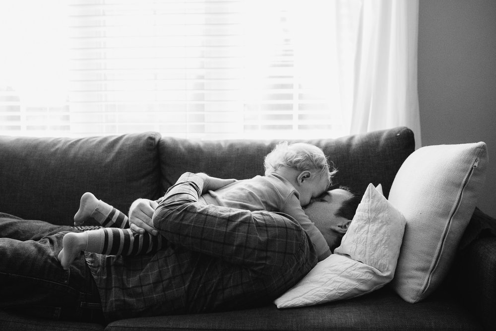 toddler boy with blonde hair lying on top of dad on couch, giving him a hug - Markham Documentary Photography