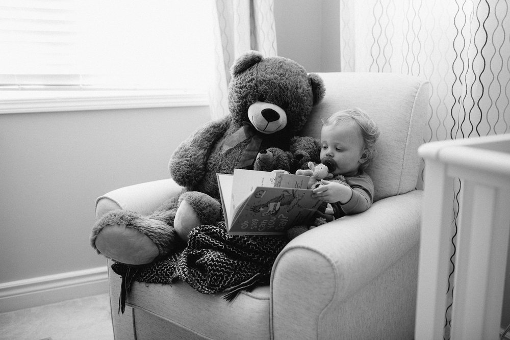 blonde 18 month boy sitting in glider with giant stuffed teddy bear reading a book - Barrie Documentary Photography