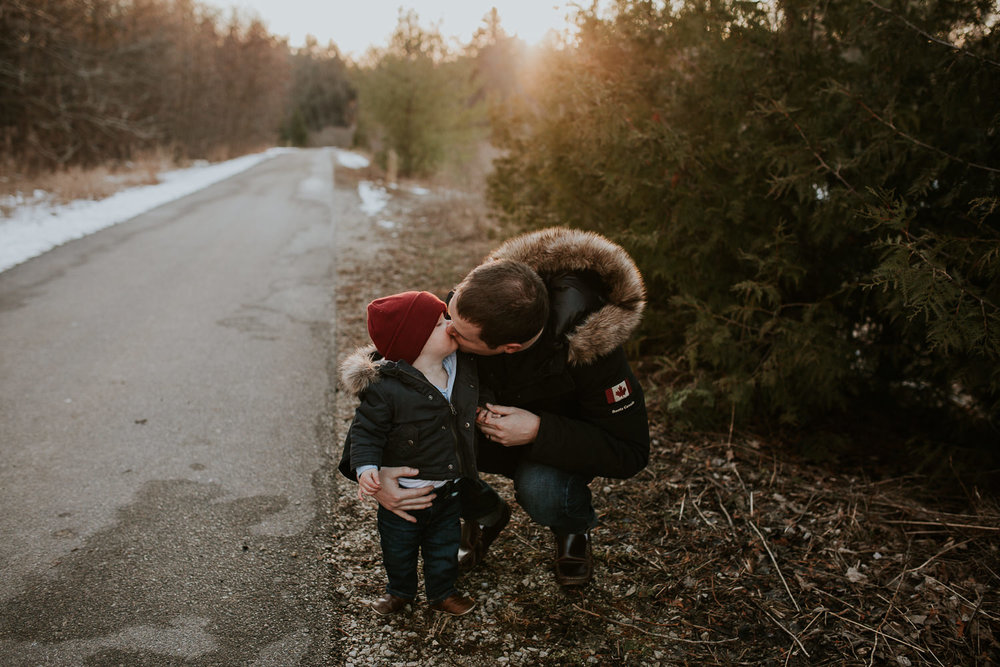18 month old boy in red hat and parka kissing his dad on a wooded trail - Newmarket Family Photographs