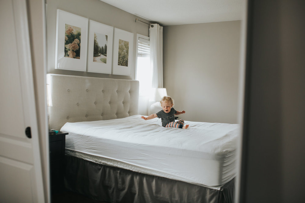 18 month old boy with blonde hair jumping on parent's bed - Stouffville Documentary Photographs