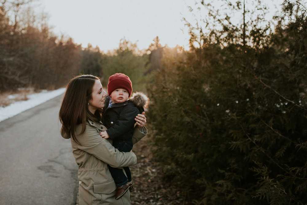 mom holding 18 month old boy in red hat in the woods at sunset - Stouffville Family Photographs