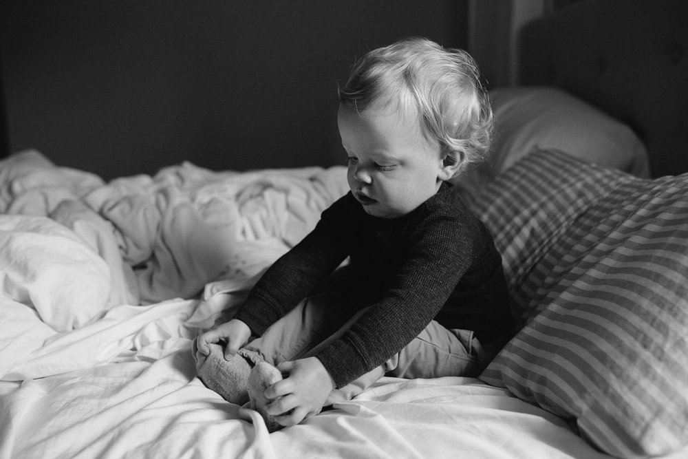 blonde 18 month toddler sitting on bed holding his feet - Markham Documentary Photographs