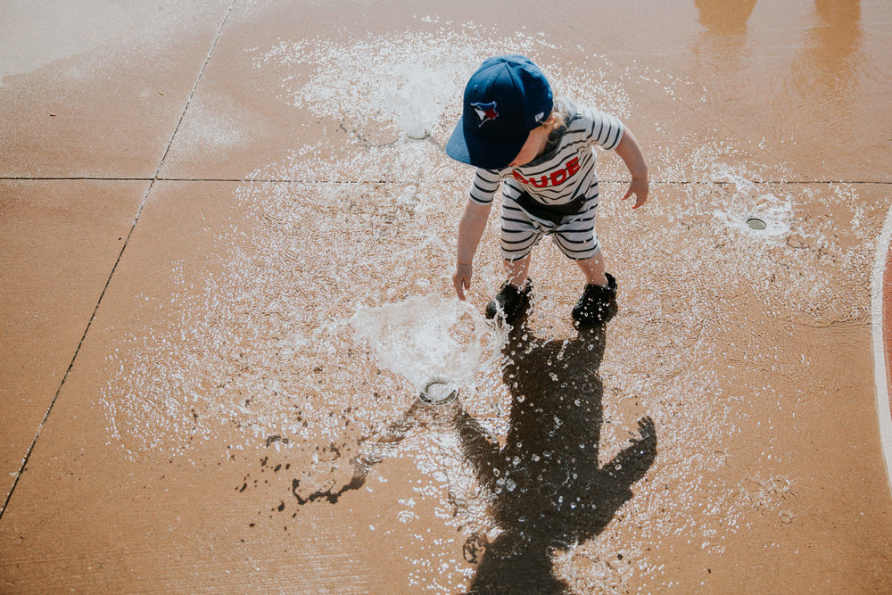 toddler boy in baseball cap playing at water splash pad -  Barrie Documentary Photographer