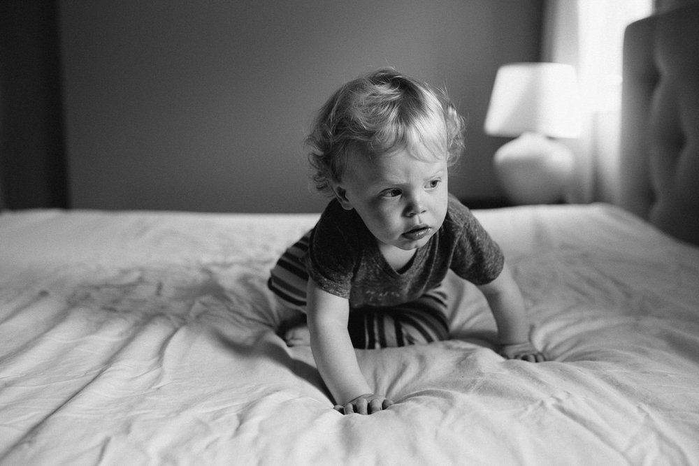 toddle boy with curly hair crawling on bed, looking to the side - Barrie Documentary Photographs