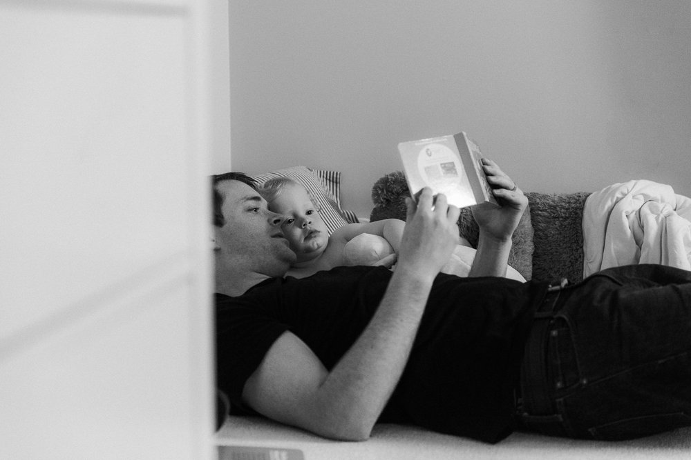 dad and toddler son lying on floor reading bedtime story - Newmarket Documentary Photography