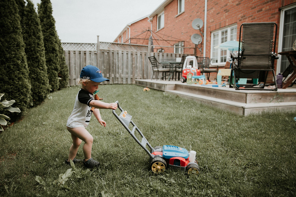 20 month old boy pushing toy lawn mower across backyard - Stouffville Documentary Photography