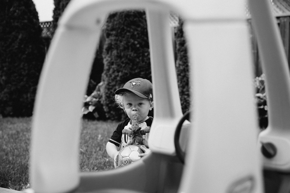 toddler boy in baseball cap with soother in mouth playing in backyard, looking at camera - Markham Documentary Photography