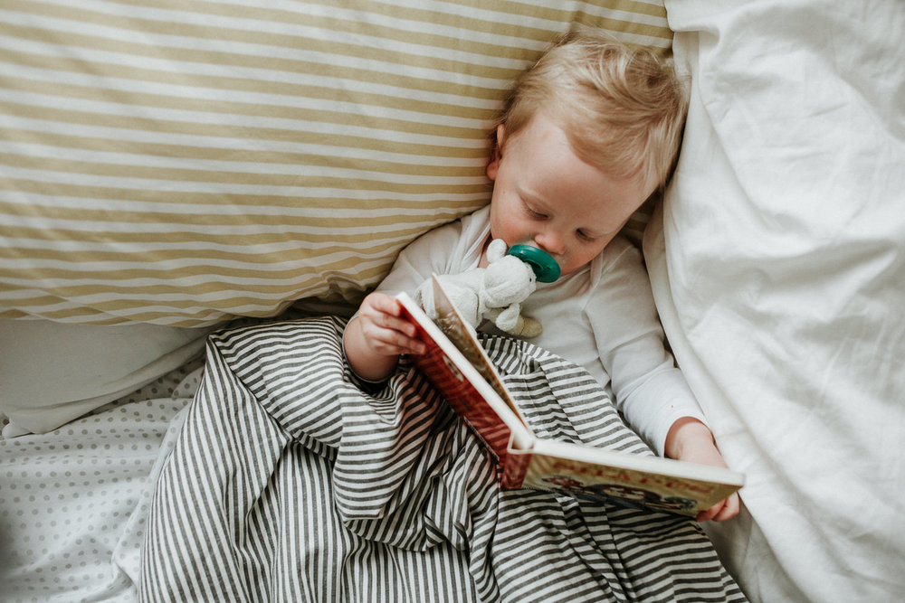 18 month old blonde boy lying in bed with striped linens, reading book - Stouffville Family Photography