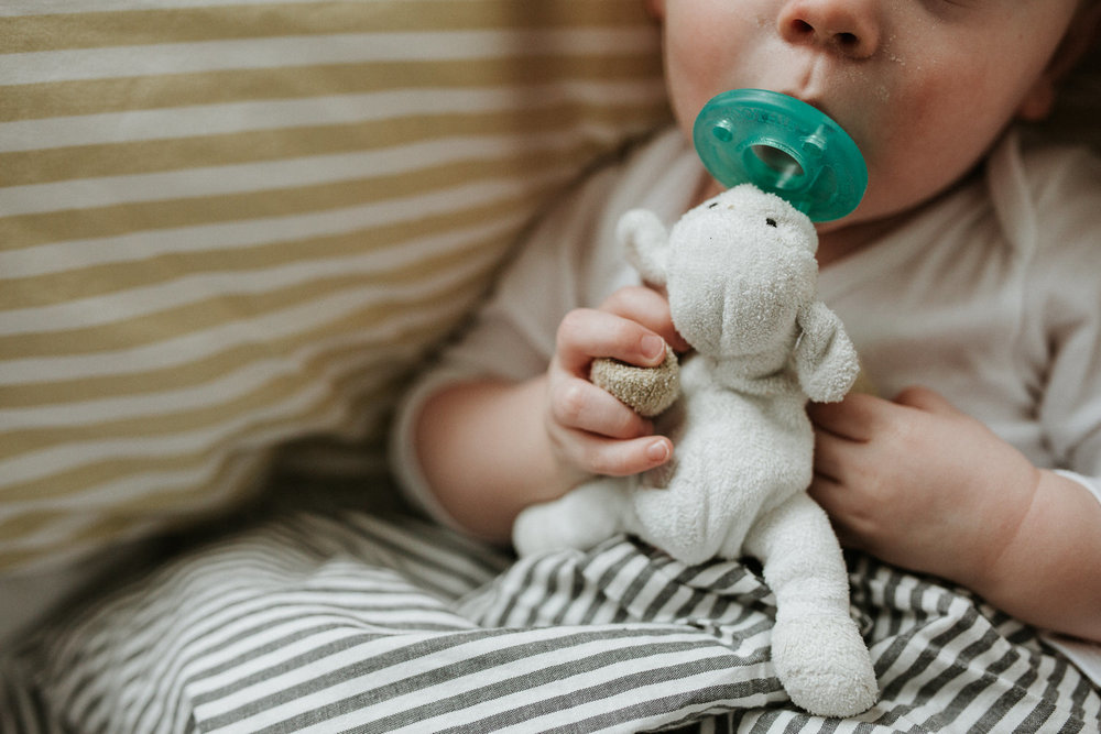 toddler lying in bed with striped linens, close up of him holding wubbanub soother - Markham Family Photography