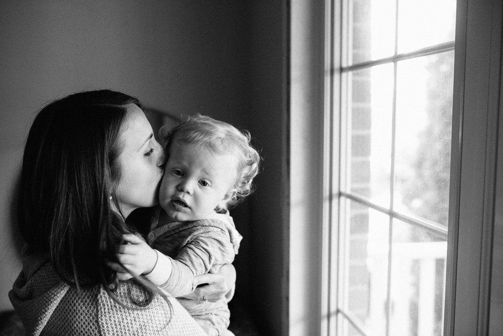 mom kissing 18 month old son on cheek, standing by window - Newmarket Family Photography