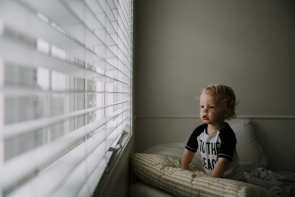 toddler boy with curly blonde hair sitting on bed looking out window at a thunderstorm - Markham Family Photography