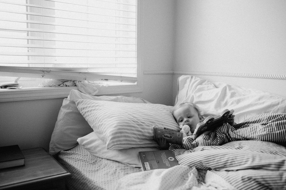 18 month old boy lying in bed choosing a book to read - Barrie Family Photography