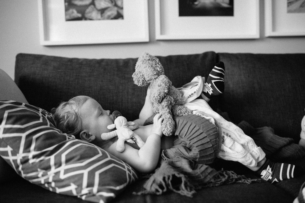 toddler lying on couch with soother in his mouth, holding and looking at teddy bear - Newmarket Family Photography