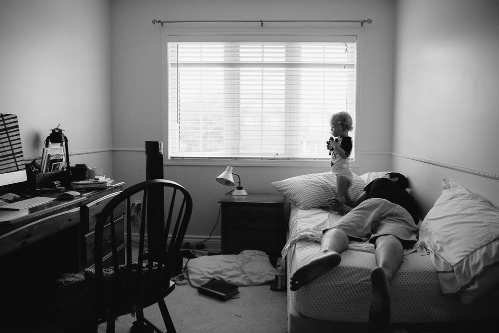 toddler boy standing on bed and dad sleep on bed - Barrie Family Photography