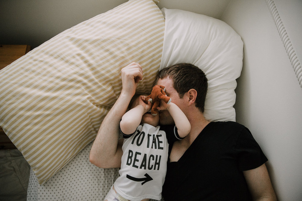 Father and toddler son lying on bed, dad kissing boy on cheek - Newmarket Family Photographer