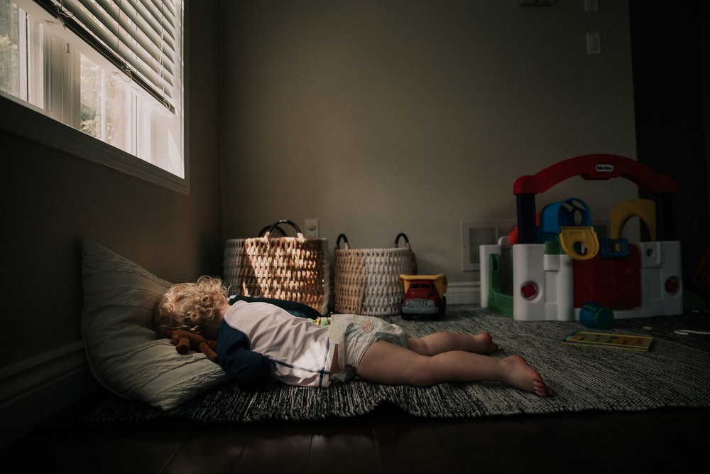 toddler boy in diaper sleeping on floor, face down - Stouffville Family Photographer