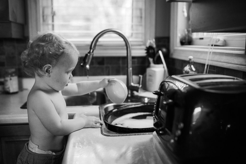 blonde toddler boy playing at kitchen sink with bowl and water - Newmarket Family Memories