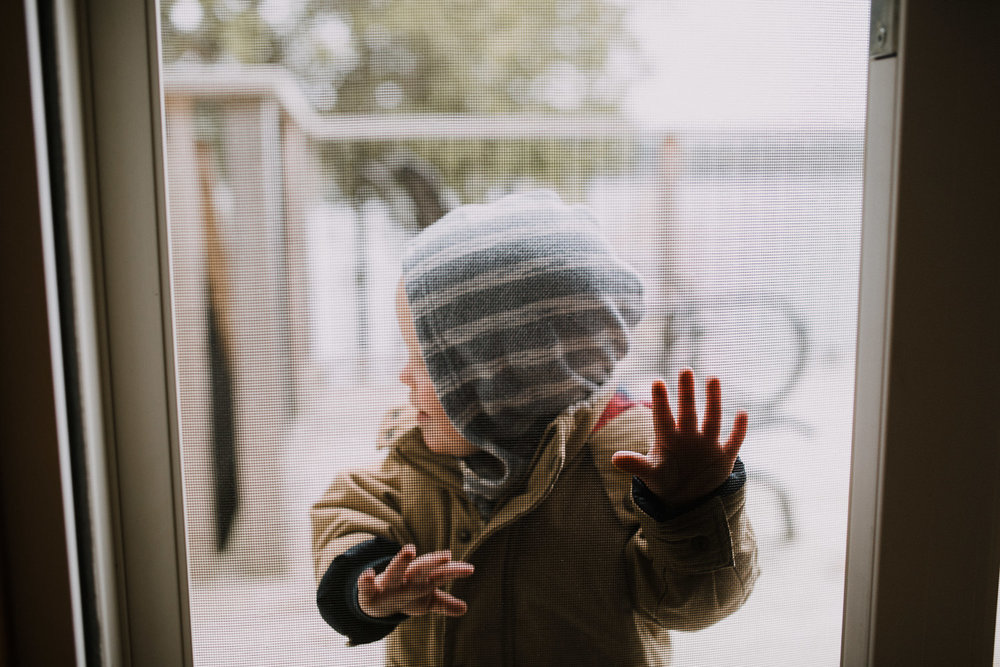 toddler boy in coat and hood outside, pressing hands against screen door - Markham Documentary Photographer