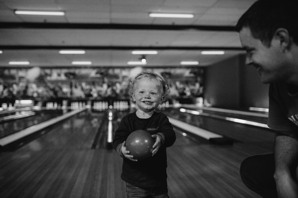 18 month old boy standing in bowling lane holding ball and smiling, dad off to side - Stouffville Family Memories