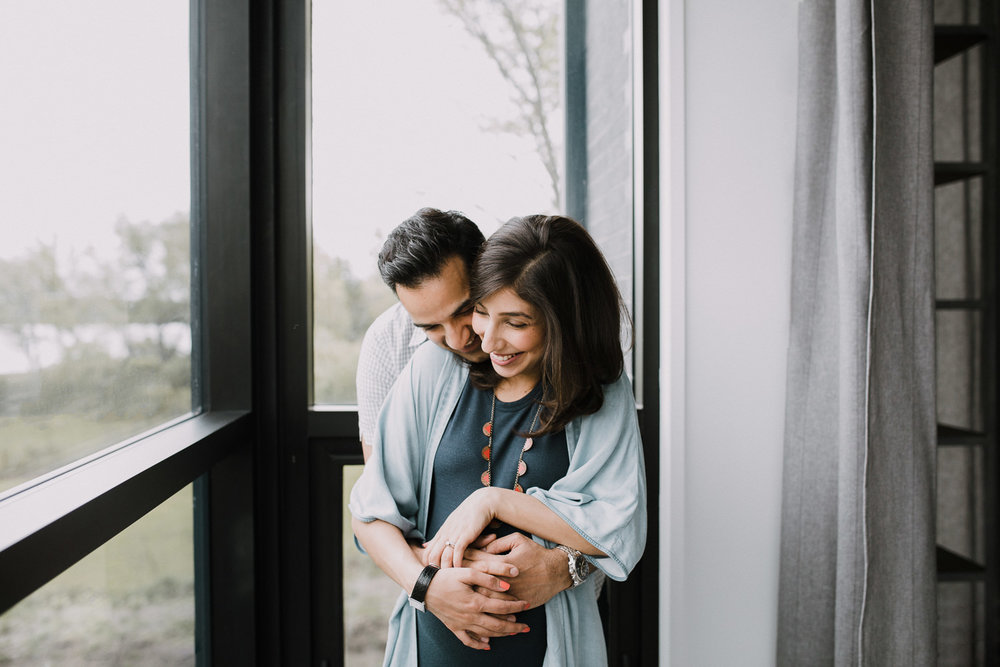 husband embraces pregnant wife from behind, standing next to window - Newmarket Lifestyle Photography