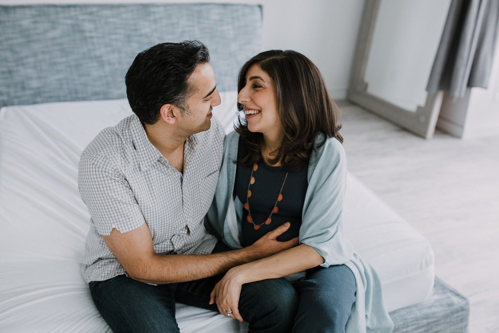 expectant parents sitting at end of bed, pregnant wife smiling at husband - Markham In-Home Photos