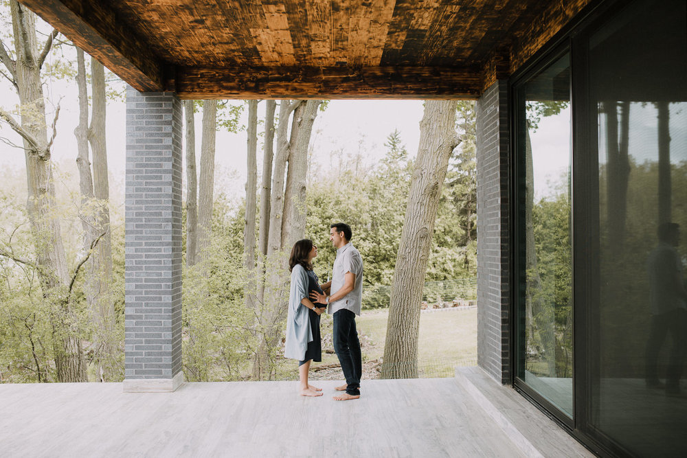 couple standing on patio facing one another, husband bolding wife's pregnant belly - Newmarket Lifestyle Photography