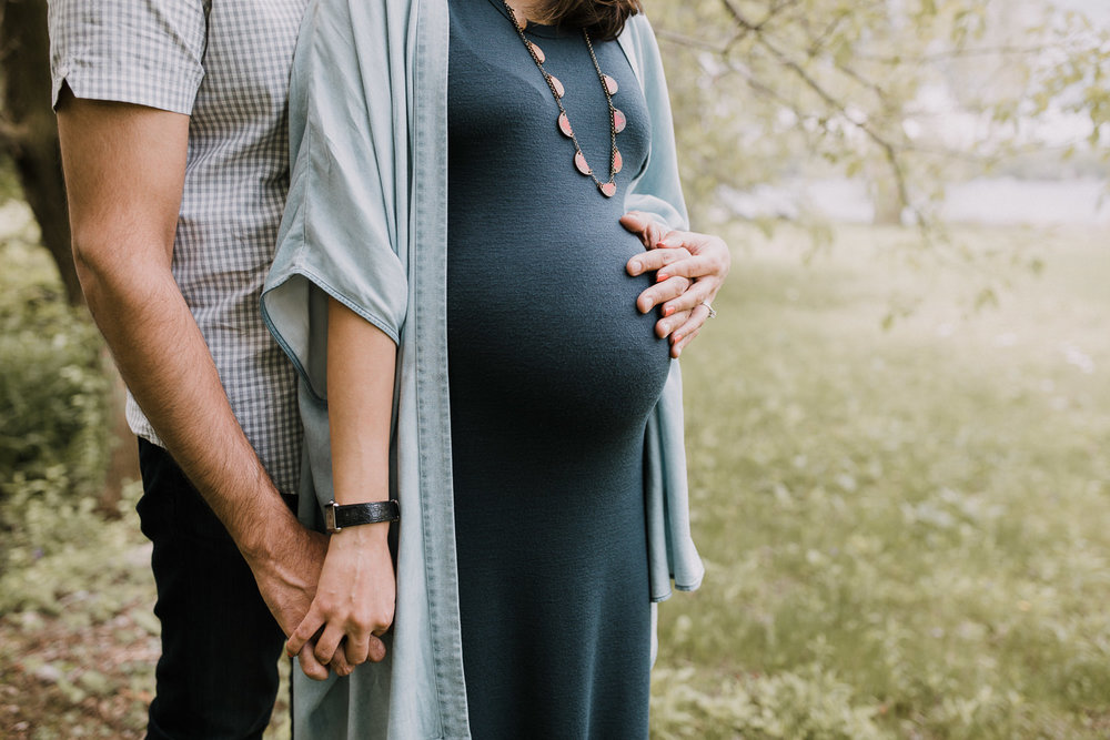 husband standing behind pregnant wife, holding her hand and touching her pregnant belly - Newmarket In-Home Photography