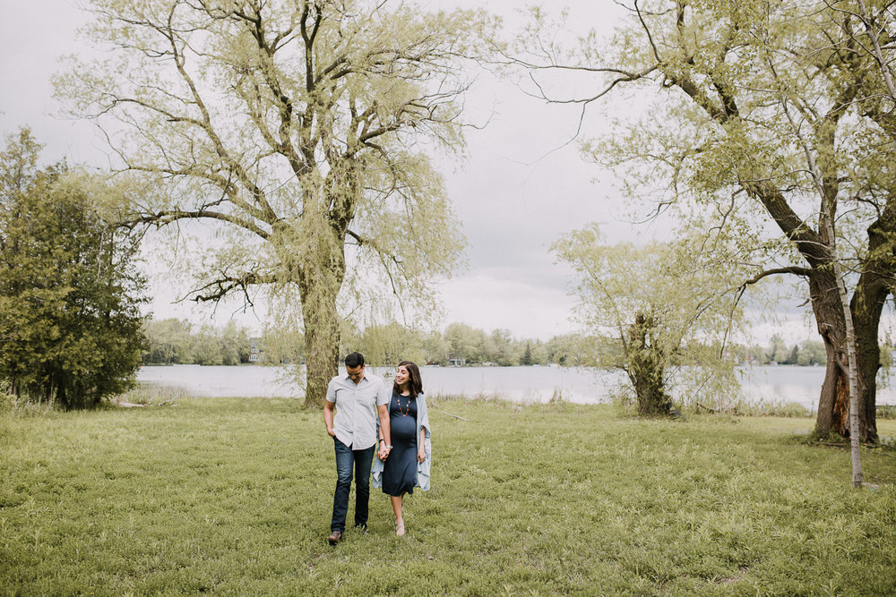 parents-to-be holding hands and walking away from the lake - Stouffville In-Home Photos