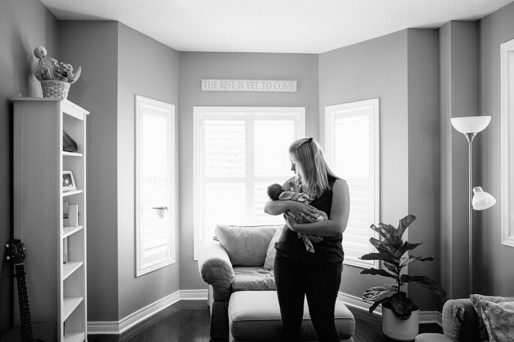 new mom standing in front of window rocking 2 week old baby boy to sleep - Newmarket Lifestyle Photography