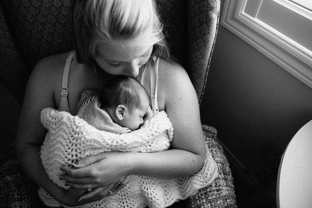 new mom sitting in rocking chair with 2 week old baby boy sleeping snuggled to her chest - Markham Lifestyle Photography
