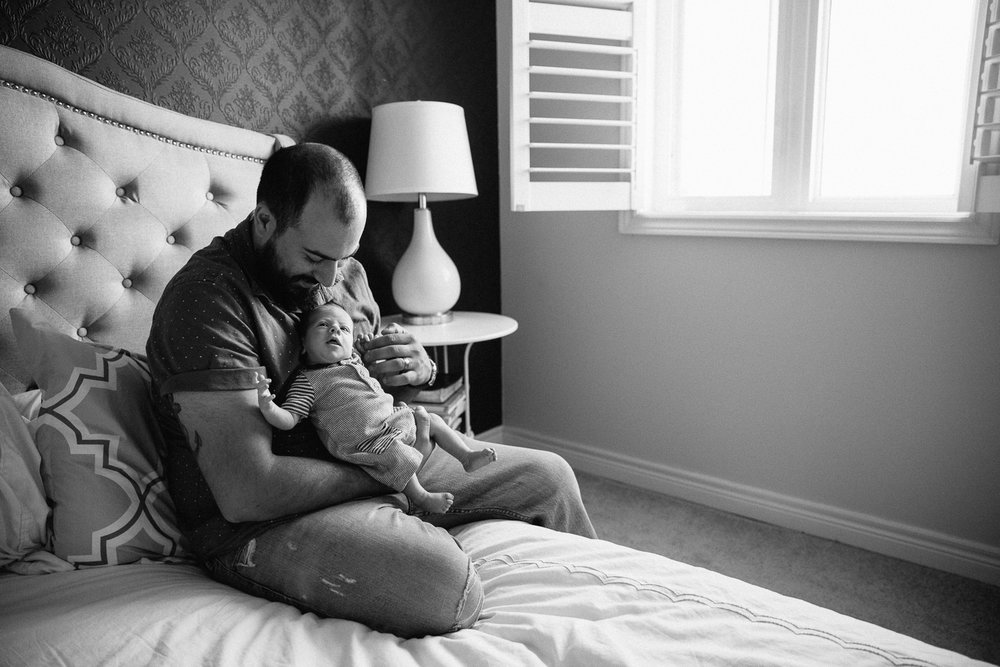 first time dad sitting on edge of bed holding 2 week old baby son - Newmarket Lifestyle Photos