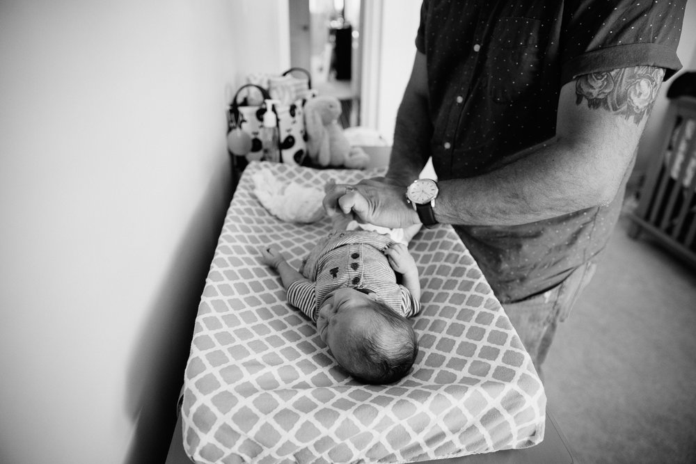 dad changing 2 week old baby boy's diaper in nursery - Markham Lifestyle Photos