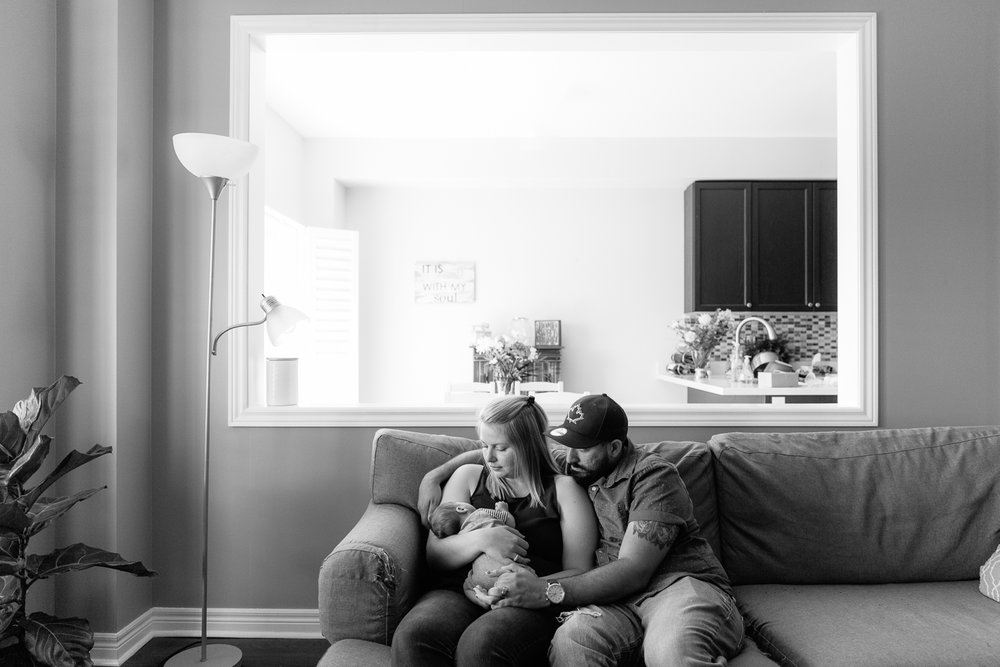 new parents sitting on couch holding and looking at 2 week old baby son - Barrie Lifestyle Photography